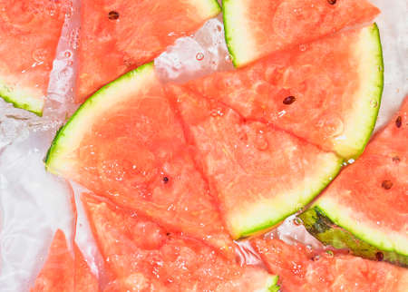 Slices of melon in water on white background. Melon close-up in liquid with bubbles. Slices of red ripe melon in water. Macro image of fruits in water