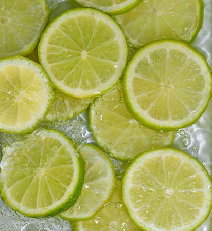 Close-up fresh slices of limes on white background. Slices of limes in sparkling water on white background, closeup. Citrus soda