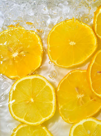 Close-up fresh slices of yellow lemon on white background. Slices of lemon in sparkling water on white background, closeup. Citrus soda