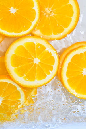 Close up view of the orange slices for lemonade background. Texture of cooling sweet summers drink with macro bubbles on the glass wall. Flat design