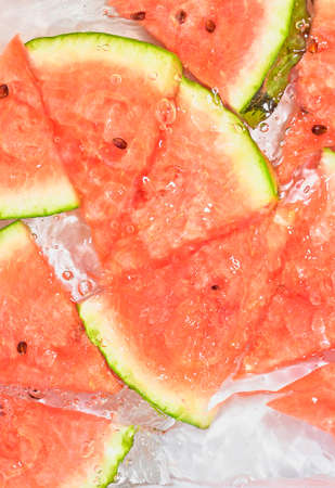 Close up view of the red melon slices in lemonade background. Texture of cooling sweet summers drink with macro bubbles on the glass wall. Flat design