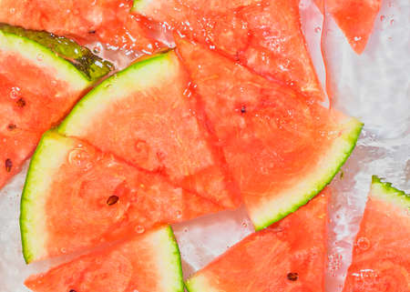 Melon close-up in liquid with bubbles. Slicec of red ripe melon in water. Close-up fresh slices of red melon on white background Standard-Bild