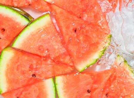 Melon close-up in liquid with bubbles. Slices of red ripe melon in water. Close-up fresh slices of red melon on white background