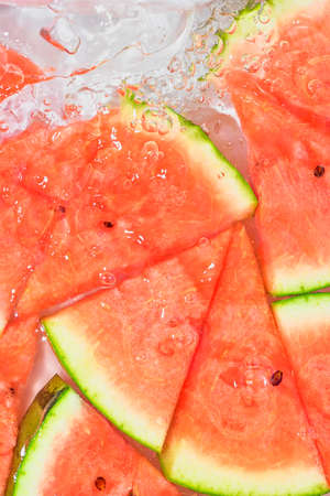 Close-up fresh slices of red melon on white background. Slices of melon in sparkling water on white background, close-up. Copy space Standard-Bild