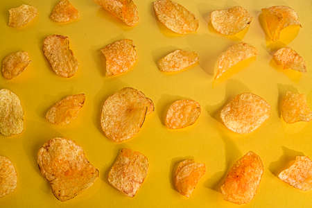 Close-up of potato chips or crisps on pastel yellow background. Cinema concept with many potato chips on yellow retro background Standard-Bild