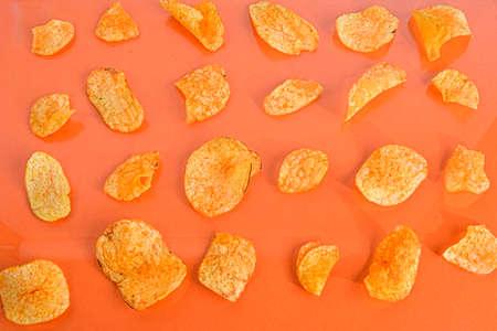 Potato chips or crisps on orange background. Movie background. Top view or flat lay. Potato chips on a pastel orange background, top view. Cinema Concept. Flat lay