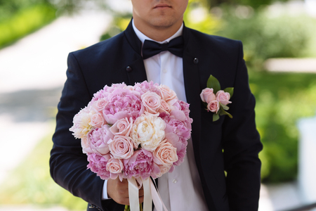 arm bouquet: groom hold wedding bouquet in his hand