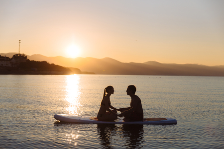 siervo: Silhouette of beautiful couple with sup serf and paddle at the ocean