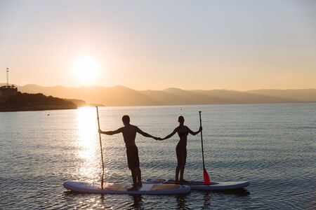 sup: Silhouette of beautiful couple with sup serf and paddle at the ocean