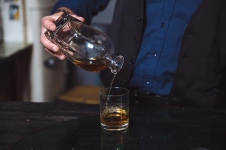 addictive drinking: Businessman pouring whiskey in his glass. Alcohol