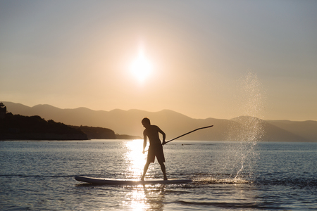 silhouette of young boy paddle boarding at sunset. concept of lifestyle sport Stock Photo