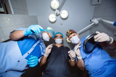 Below view of surgeons team holding medical instruments in hands. Concept of a healthy