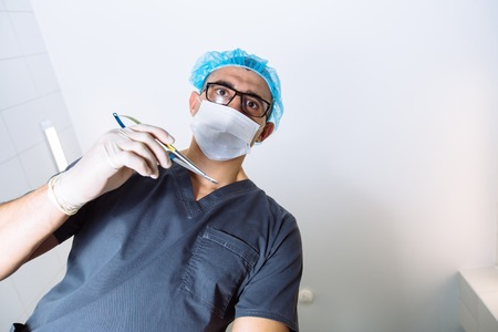 physicals: Below view of surgeon holding medical instruments in hands. Concept of a healthy
