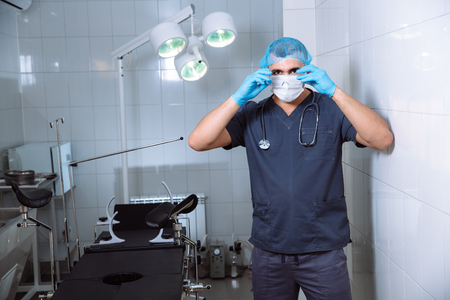 protective: Young man surgeon takes on protective glasses after operation in hospital.