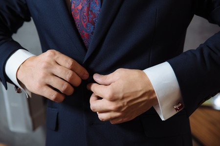 cuff link: man wears a black jacket. concept of business