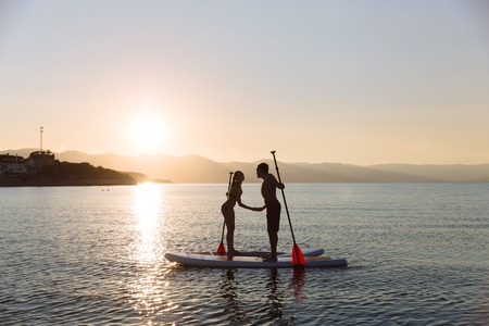 sup: Silhouette of kissing male and female on sup surf at the ocean. Concept lifestyle, sport, love.