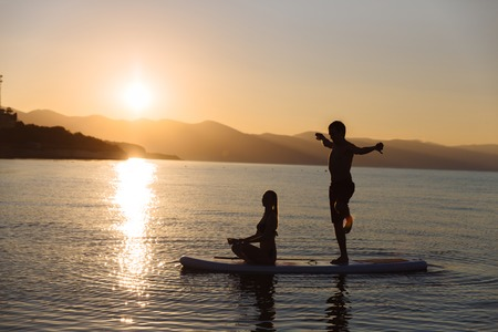 sup: Silhouette of boy in yoga pose and girl sitting on sup surf at the ocean. Concept lifestyle, sport