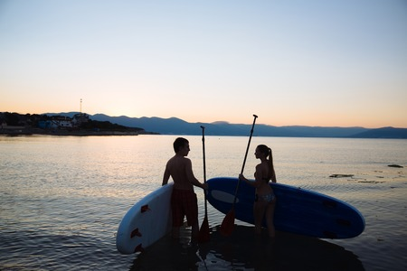 sup: Silhouette of beautiful couple looking at each other with sup surf and paddle, the ocean. Concept sport, love