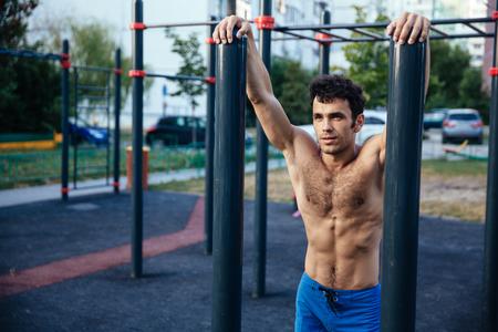 Muscular man at crossfit ground doing push ups as part of training. Sport concept Standard-Bild