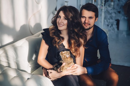 beautiful couple in love with a cat in their arms sitting on the sofa, hugging, smiling and kissing. Family concept