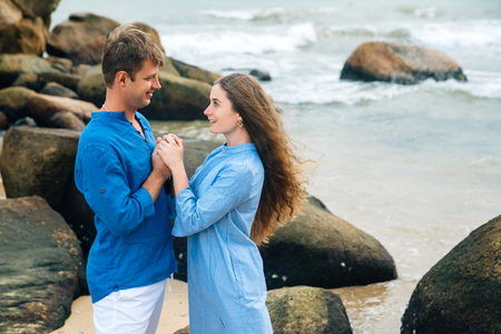 young couple in love in blue shirt holding hands on the beach and looking at each other. Sea big stones background. Concept of family