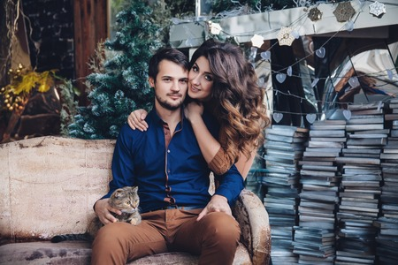 taking a wife: beautiful couple in love with a cat in their arms sitting on the sofa, hugging, smiling and kissing. Family concept