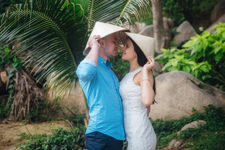 teen golf: couple in love hugging in beautiful place with palm trees in summer. man wear the blue shirt and the girl in a white dress with vietnamese hats on their heds. Concept of honeymoon