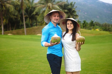 Young beautiful couple in love holding coconut in hands and walking at golf course in summer. man wear the blue shirt and the girl in a white dress and vietnamese hats. Concept of honeymoon Stock Photo