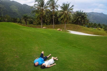 teen golf: Young beautiful couple holding hands, lying at green grass of golf course in summer. man wear the blue shirt and the girl in a white dress. Concept of honeymoon Foto de archivo
