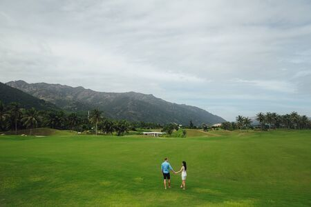 passion fruit flower: Young beautiful couple in love holding hands and walking at golf course in summer. man wear the blue shirt and the girl in a white dress. Concept of honeymoon Stock Photo