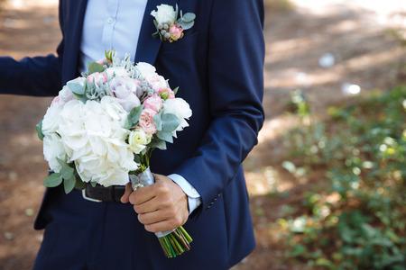 Wedding bouquet in groom hands, close up Stock Photo