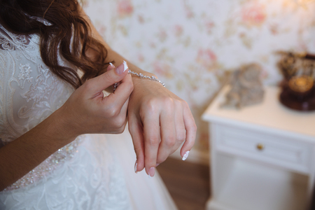 The bride puts the bracelet on her arm, close up Stock Photo