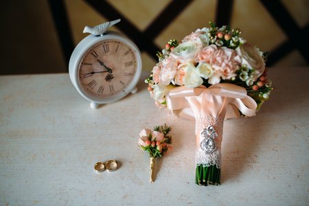 Wedding accessories. Boutonniere, Golden rings, a beautiful bouquet of flowers on white textured table. Concept of bride and groom ornamentation