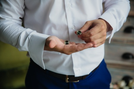 cuff link: Groom hands with cufflinks. Elegant gentleman clother, white shirt