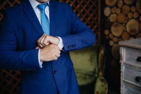 cuff link: Groom hands wearing cufflinks. Elegant gentleman clother, white shirt blue jacket