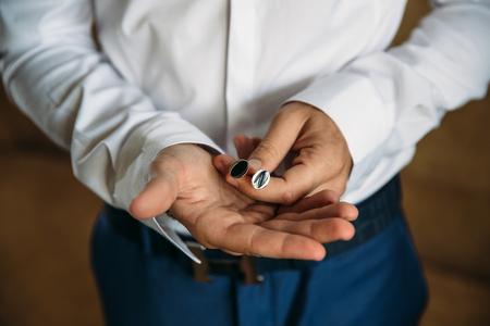 cuff link: Groom hands with cufflinks. Elegant gentleman clother, white shirt and brown belt Stock Photo