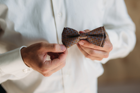 Closeup Groom hands with bow-tie. Elegant gentleman clother, white shirt and brown belt Stock Photo