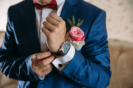 Man in blue jacket with boutonniere wear wrist watches. Concept of jewelry, dress