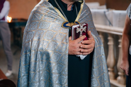 The Holy Cross in the hands of a priest, close up Stock Photo