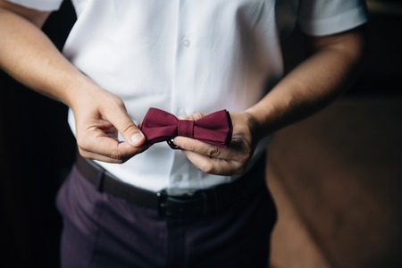 Close-up businessman groom holding bow-tie in his hands. Concept of men stylish elegance clothes