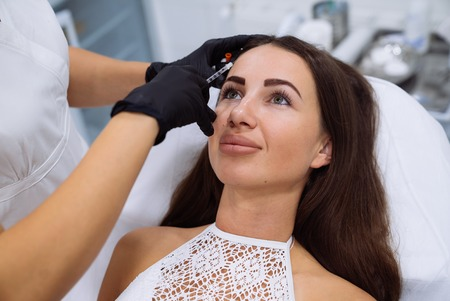 Close up beautiful female face and cosmetologists hands with syringe during facial beauty injections. Botox pricks, hyaluronic acid injection. Rejuvenation and hydratation. Cosmetology concept