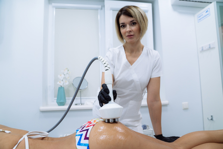 A female doctor makes manipulations with the patient on the body and ass. Radio frequency lifting. Medical tools, instruments