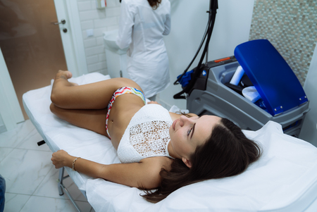 Woman with a good figure lies on the table, manipulating the patient on the body. Radio frequency lifting. Medical instruments, doctor on background Imagens