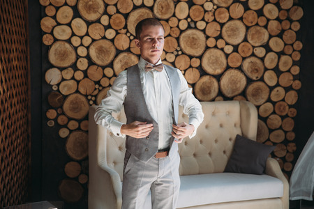 A man dresses a waistcoat in the morning in the studio with a wooden background. Blond businessman in strict business attire. preparation of the groom for the wedding day. The concept of business clothes in the office. Stock Photo