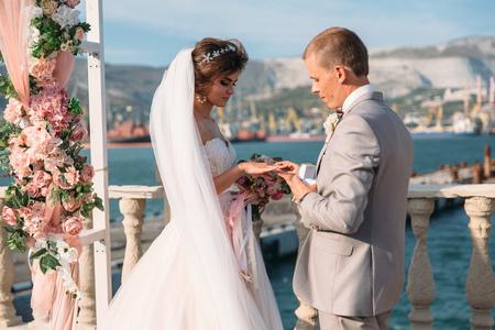 Paar im Hochzeitsbogen tauscht Ringe mit See auf Hintergrund aus, die Braut mit langen schönen Haaren und Bräutigam im schwarzen Anzug schauen sich am Hochzeitstag an. Konzept der Liebe und Familie