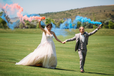 The bride and groom with smoke bombs on a field with green grass. Newlyweds walking outdoors at wedding day. Girl in luxury long white dress and man in business grey suit.