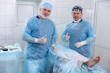 Team of doctors in sterile medical gowns perform surgery in a surgical room. Surgeon with an assistant after the procedures show OK sign with hands, thumb lifted up. Portrait of medical workers. Imagens