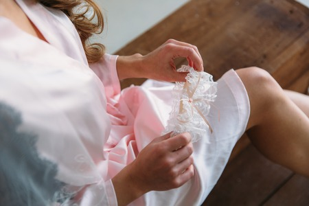 Morning of the bride. Close-up of young bride in pink dressing-gown putting on white garter at the wedding day. Hands of the girl with accessories. Фото со стока