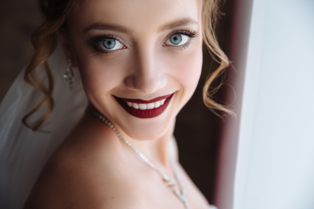 Close-up of a blonde with curls smiling snow-white teeth and dark lips. A girl with big gray beautiful eyes. Morning of bride at wedding day, preparations.