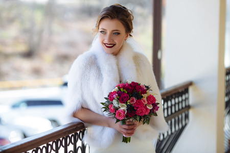 The bride is standing on the porch, dressed in woolen white, and smiling at her guests who have just arrived. The girl is holding a beautiful fragrant bouquet of flowers. Фото со стока
